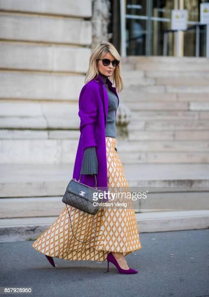 Gitta Banko wearing a long creamwhite Aline skirt with mustard colored Bauhaus pattern by Dawid Tomaszewski grey trumpet sleeve sweater by Steffen...