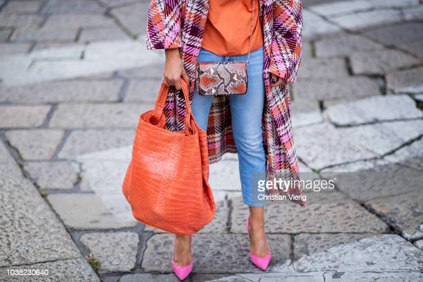 Gitta Banko wearing a multicolored checked coat by Dawid Tomaszewski an orange statement blouse by Redirection jeans by Closed mini python purse and...