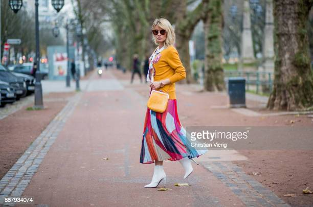 Gitta Banko wearing a multicolored pleated dress by Steffen Schraut pearl colored tieneck blouse with floral and butterfly print by Steffen Schraut...