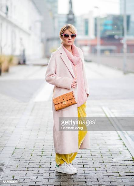 Gitta Banko wearing a pink cashmere turtleneck sweater with cutouts on the shoulders by The Mercer NY yellow velvet trousers by Mango lightpink...
