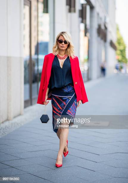 Gitta Banko wearing a red fitted blazer by Steffen Schraut blue silk blouse with deep Vneck by Bash red stingray leather oversize necklace by a...
