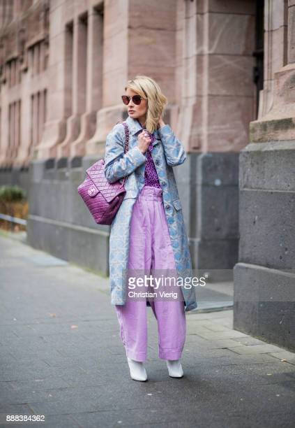 Gitta Banko wearing a silvergrey coat with lightblue pattern by Dawid Tomaszewski purple blouse with bird print by HUGO lavender colored high waist...