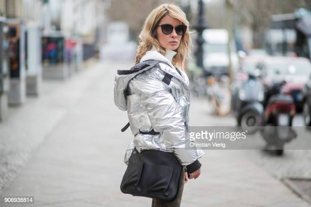 Gitta Banko wearing a silvermetallic down jacket and camouflage patterned jeans by True Religion white cotton blouse with large pleated sleeves and...
