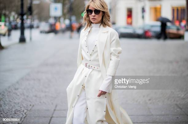 Gitta Banko wearing a total Agnona look containing a white silk longsleeve shirt white silkcottonmix trousers ivory colored long vest with tiny blue...