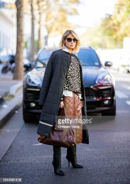 Gitta Banko wearing a white blouse by Danny Reinke leopard sweater by Steffen Schraut brown leather skirt by Liviana Conti black oversize daunen coat...