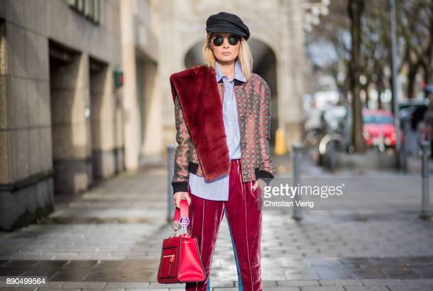 Gitta Banko wearing bordeaux velvet pants with blue stripes and a grey bomber jacket with Bordeaux pattern by Dawid Tomaszewski with a fake fur scarf...