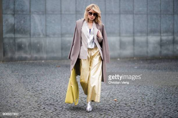 Gitta Banko wearing golden paper trousers by MM6 Martin Margiela, silver blouse from H&M, shiny beige leather blazer by Dawid Tomaszewski, taupe...