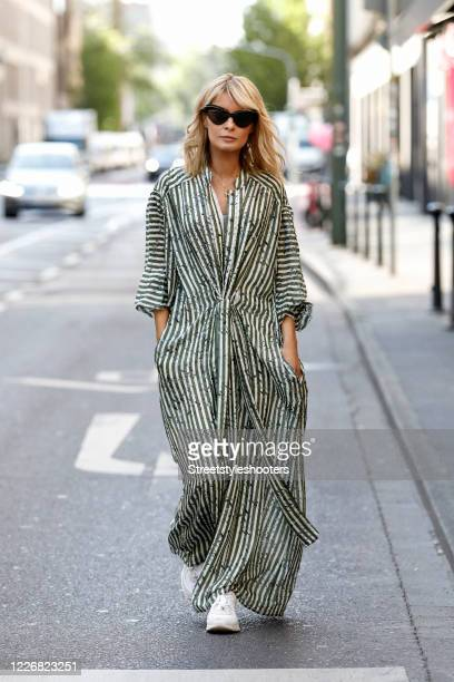 Gitta Banko, wearing sunglasses by Mykita x Maison Margiela, a long olive green and white striped dress by LaLa Berlin and white sneaker by Chanel...
