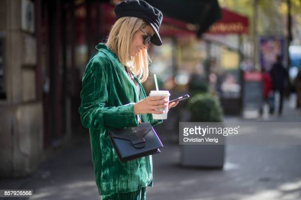 Gitta Banko with a Starbucks coffee to go and a phone texting wearing a green velvet suit by Jadicted white cotton shirt by Dsquared 2 black sock...