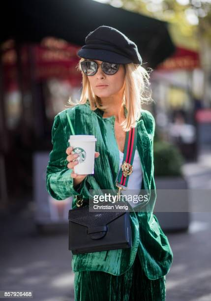 Gitta Banko with a Starbucks coffee to go wearing a green velvet suit by Jadicted white cotton shirt by Dsquared 2 black sock boots from Mango a Suzy...