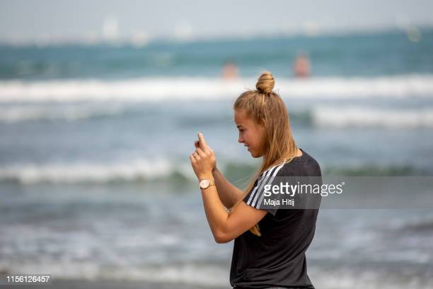 Giulia Gwinn of Germany takes pictures as team of Germany visits the beach on June 15 2019 in La GrandeMotte France