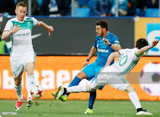 Giuliano of FC Zenit St Petersburg vies for the ball with Andrei Semyonov of FC Terek Grozny and Rizvan Utsiyev of FC Terek Grozny during the Russian...