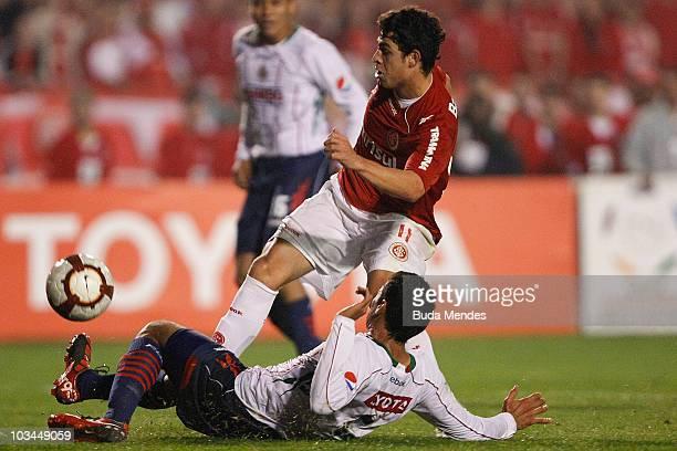Giuliano of Internacional struggles for the ball with a player of Chivas during a match as part of the 2010 Copa Santander Libertadores at Beira Rio...