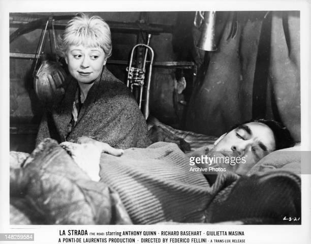Giulietta Masina watches Anthony Quinn sleep in a scene from the film 'La Strada' 1954