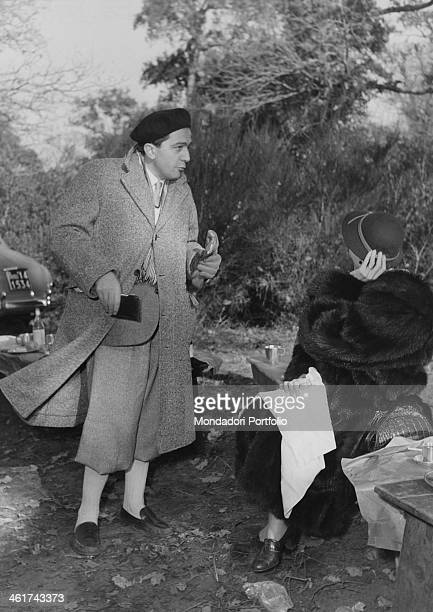 Giulio Andreotti politician of the Christian Democrats with coat and beret is standing while talking with the journalist Flora Antonioni sitting on...