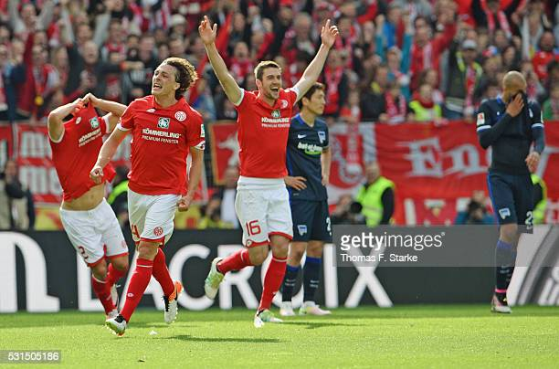 Giulio Donati Julian Baumgartlinger and Stefan Bell of Mainz celebrate while Genki Haraguchi and John Anthony Brooks of Berlin looks dejected after...