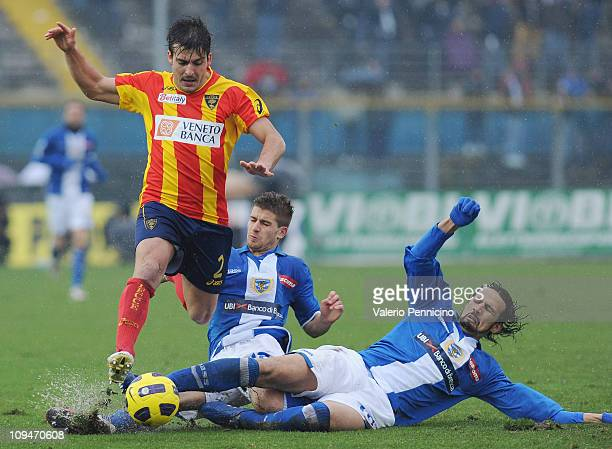 Giulio Donati of Lecce clashes with Gaetano Berardi and Victor Hugo Mareco of Brescia Calcio during the Serie A match between Brescia Calcio and...