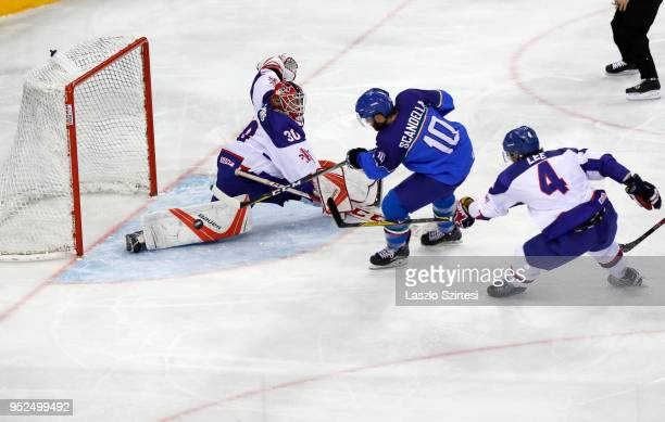Giulio Scandella of Italy scores the their equaliser among goalie Ben Bowns of Great Britain and Stephen Lee of Great Britain during the 2018 IIHF...