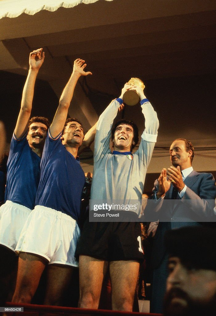 Giuseppe Bergomi, Claudio Gentile of Italy raise their arms in salute as Dino Zoff holds the winners trophy aloft as King Juan Carlos of Spain applauds after defeating the Federal Republic of Germany in the 1982 FIFA World Cup final on 11 July 1982 at the Santiago Bernabeu stadium in Madrid, Spain.Italy won the game 3-1.