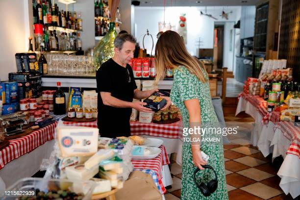 Giuseppe Calcagno, owner of Ciullosteria, an Italian restaurant turned delicatessen specialising in Italian products, recommends a pack of pasta to a...