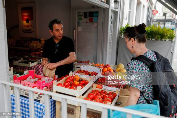 Giuseppe Calcagno owner of Ciullosteria packs a bag of tomatoes for a customer as his Italian restaurant turned into a 'deli' specialising in Italian...