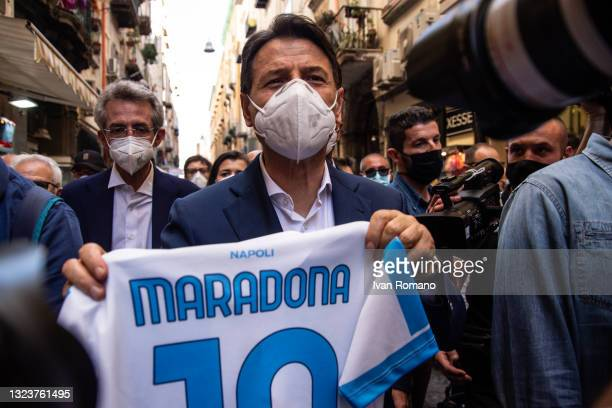 Giuseppe Conte posing with Maradona's shirt during a visit to the Pignasecca market on June 15, 2021 in Naples, Italy. The political head of the 5...