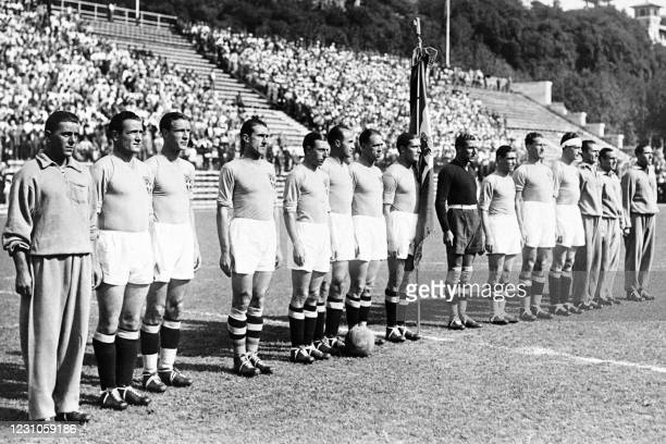 Giuseppe Meazza holding the flag and the Italian football team listen to the national anthem before the match of the World Cup's 1934 in Italy.