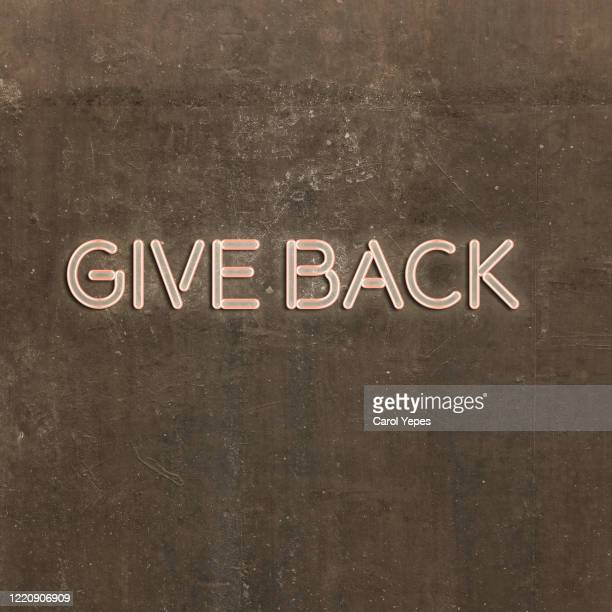 give back text in neon lights - giving tuesday stock pictures, royalty-free photos & images