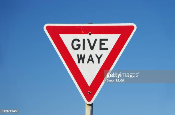 give way sign against a clear blue sky - give way stock pictures, royalty-free photos & images
