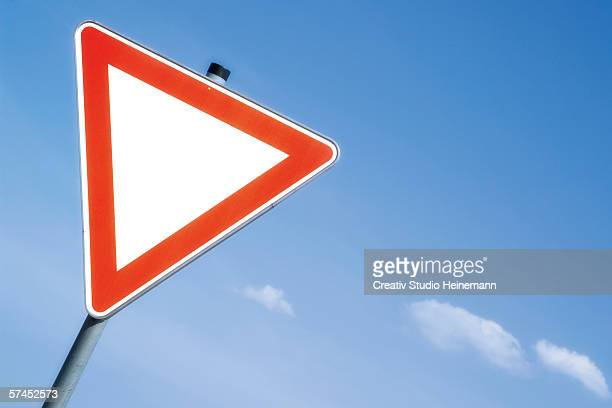 Give way board sign against sky