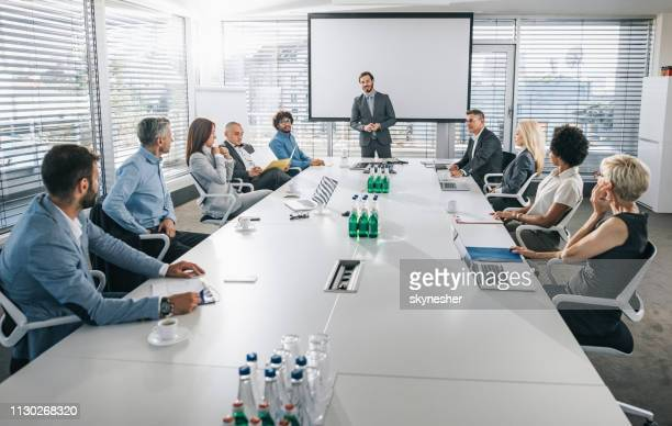 ceo giving a business presentation in front of projection screen in a board room. - tavolo da conferenza foto e immagini stock