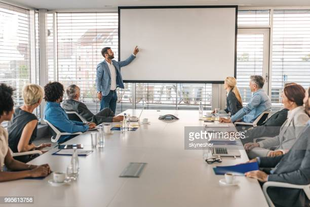 ceo giving a business presentation through projection screen in a board room. - projection screen stock pictures, royalty-free photos & images