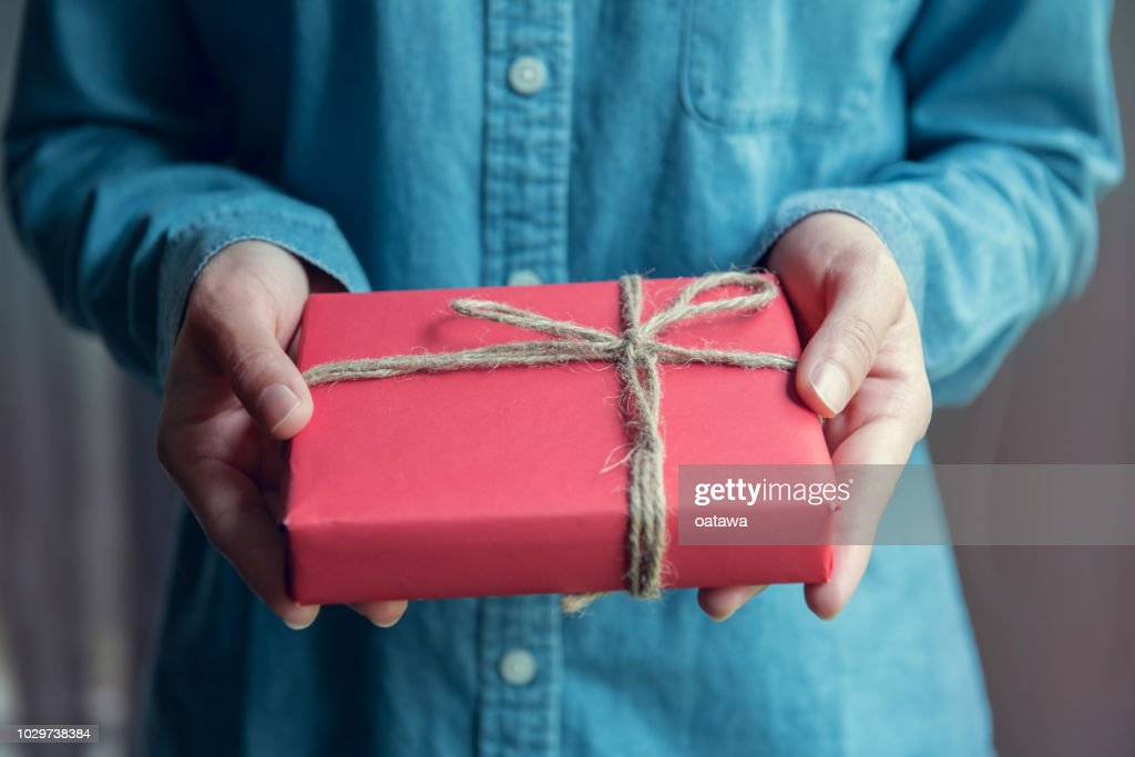 Giving a gift, Woman hands holding handmade present wrapped in red paper. : Stock Photo