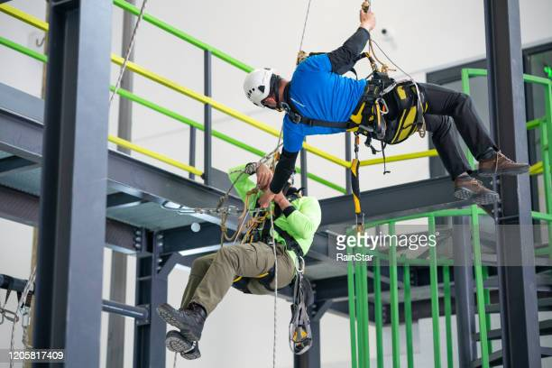 giving a helping hand - safety harness stock pictures, royalty-free photos & images