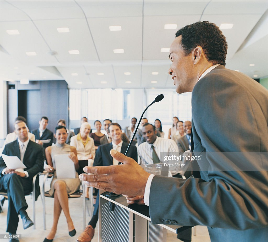 CEO Giving a Presentation to a Group of Business People from a Podium in a Conference Room : Stock Photo