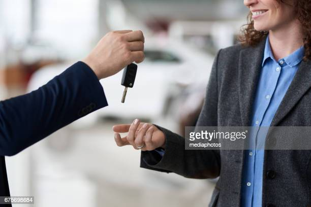 Giving car key to new owner