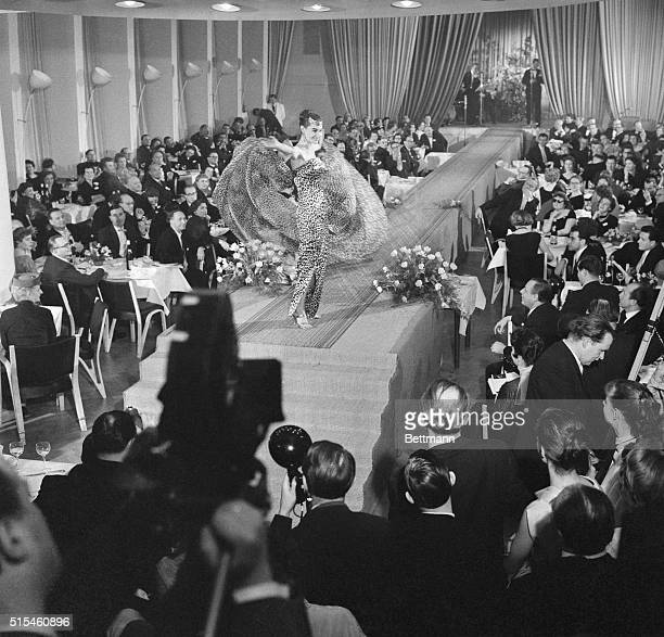 Giving dramatic effect to her performance at a West Berlin fashion show, this model twirls a huge chiffon shawl as she parades before some 200...