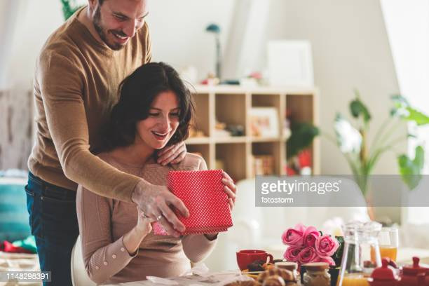 giving her a gift - valentine's day holiday stock pictures, royalty-free photos & images