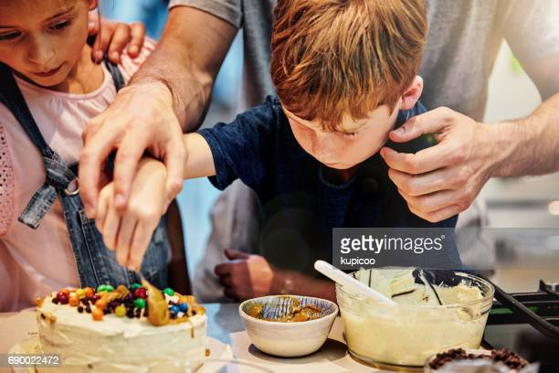 giving him a helping hand - decorating a cake stock pictures, royalty-free photos & images