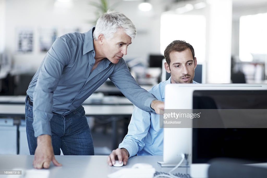 Giving his colleague some guidance : Stock Photo