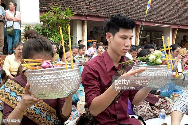 Giving offerings of candles and flowers to Buddha at the That Luang festival Vientiane Lao PDR Pha That Luang is the national symbol and most...