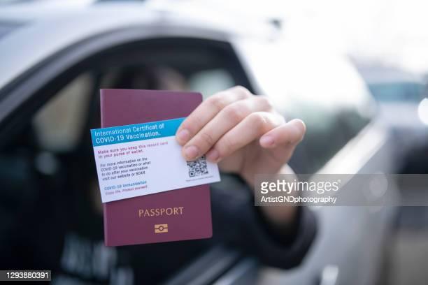 dar pasaporte y certificado de vacunación covid-19 en el control fronterizo. - pase fotografías e imágenes de stock