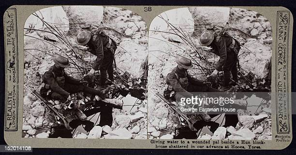 Giving water to a wounded pal beside a Hun blockhouse shattered in our advance at Hooge Ypres Belgium ca 1915