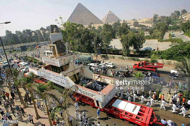 The massive statue of Ramses II passes close to the great pyramids in Giza during the end of its journey from the polluted city to a spot near the...