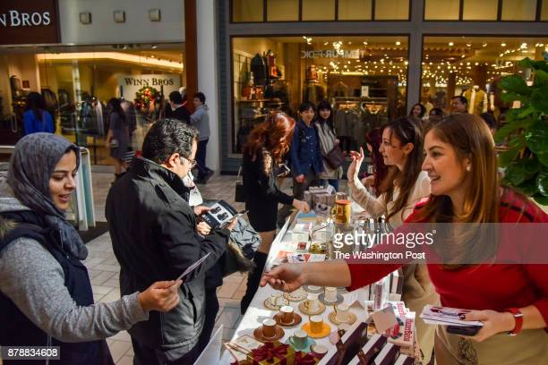 Gizem Salcigil White 2nd from R The Turkish Coffee Lady shares samples and information as consumers take to the Black Friday shopping at Tysons...