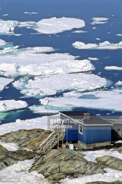 Glaces du pack de la banquise derivant apres la debacle devant une maison traditionnelle du petit village inuit de Tiniteqilaaq Region d'Ammassalik