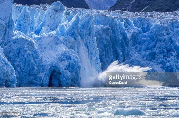 glacier calving into alaskan bay - glacier collapsing stock pictures, royalty-free photos & images