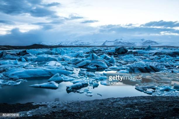 ghiacciaio in islanda - iceberg blu che galleggiano nella laguna - clima polare foto e immagini stock