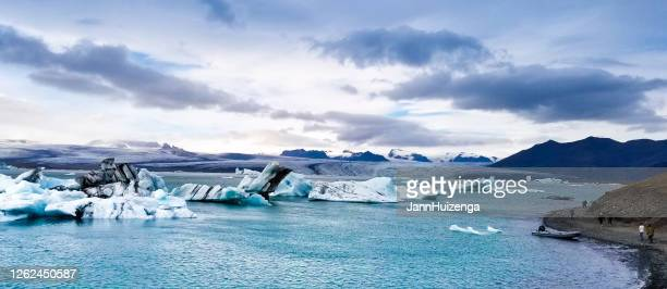 アイスランドの氷河ラグーン:氷山でラグーンの近くを歩く人々 - 氷河湖 ストックフォトと画像