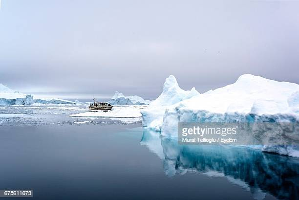 glacier on frozen lake against sky - north pole stock pictures, royalty-free photos & images